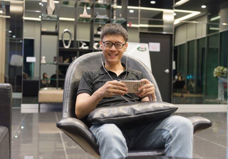 Asiatischer Mann, der einen Smartphone im Wohnzimmer nachts verwendet lizenzfreies stockbild