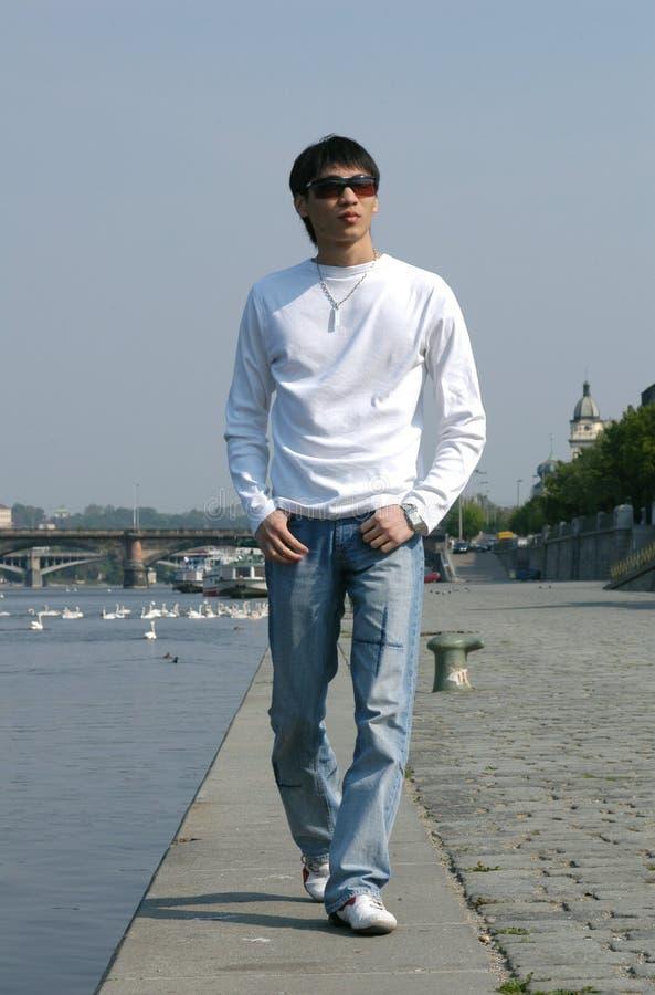 Asiatischer Mann, der entlang den Damm geht lizenzfreie stockfotografie