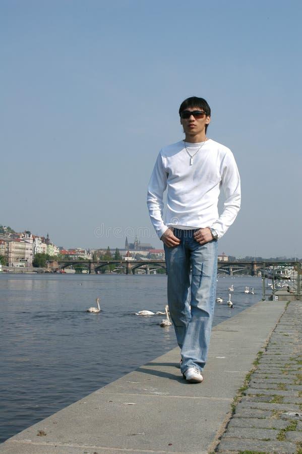 Asiatischer Mann, der entlang den Damm geht stockfoto