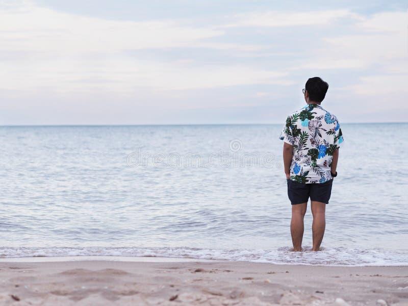 Asiatischer Mann, der entspannt morgens auf Sand entlang dem Strand allein steht stockbilder