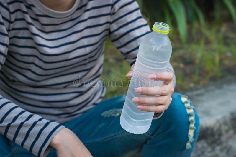 Asiatischer Mann, der Flasche Wasser sitzt und hält stockfoto