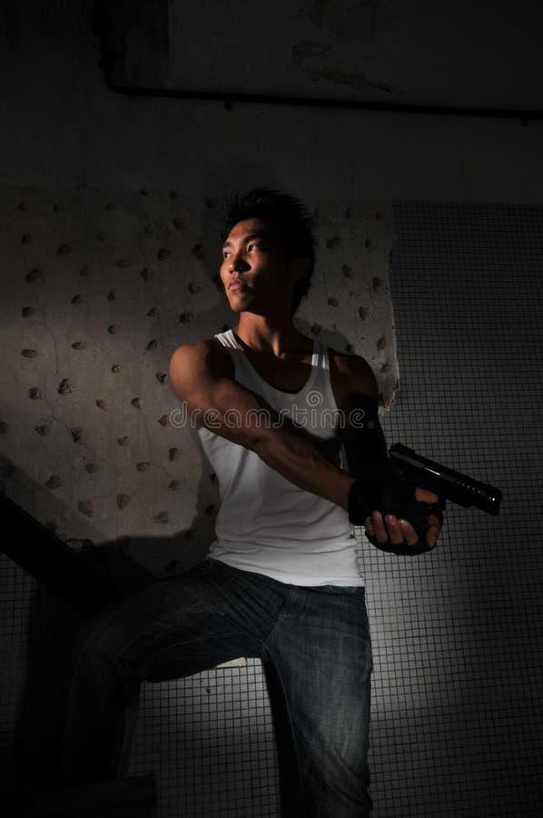 Asiatischer Mann, der im Treppenhaus trägt eine Gewehr sich versteckt stockfotos