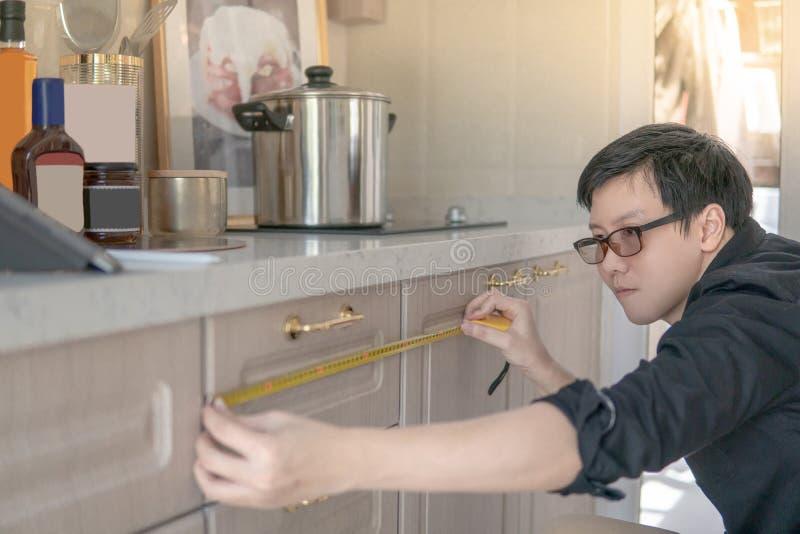 Asiatischer Mann, der Maßband auf Küchenarbeitsplatte verwendet lizenzfreies stockbild