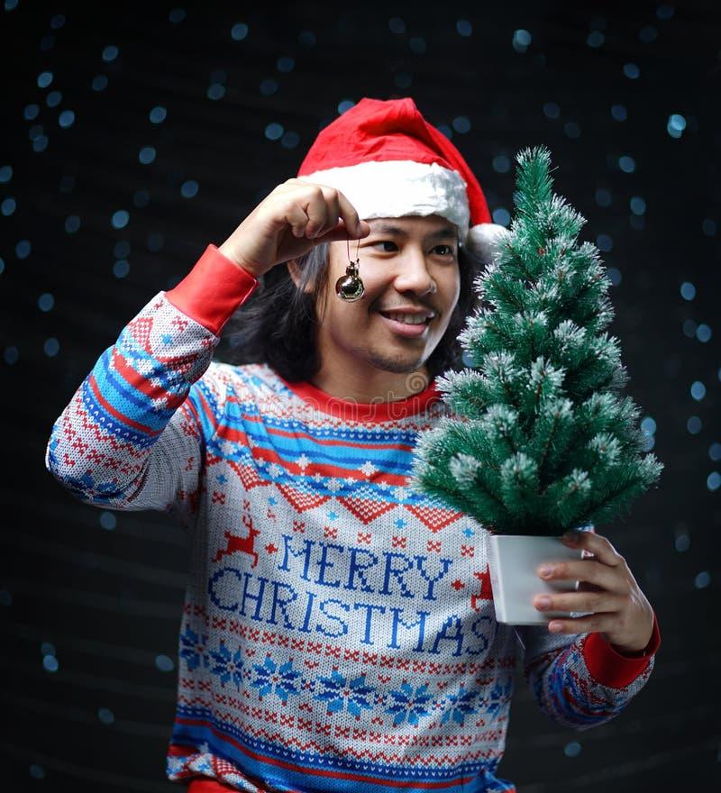 Asiatischer Mann, der Santa Hat und Weihnachtsstrickjacke halten klein trägt lizenzfreies stockbild