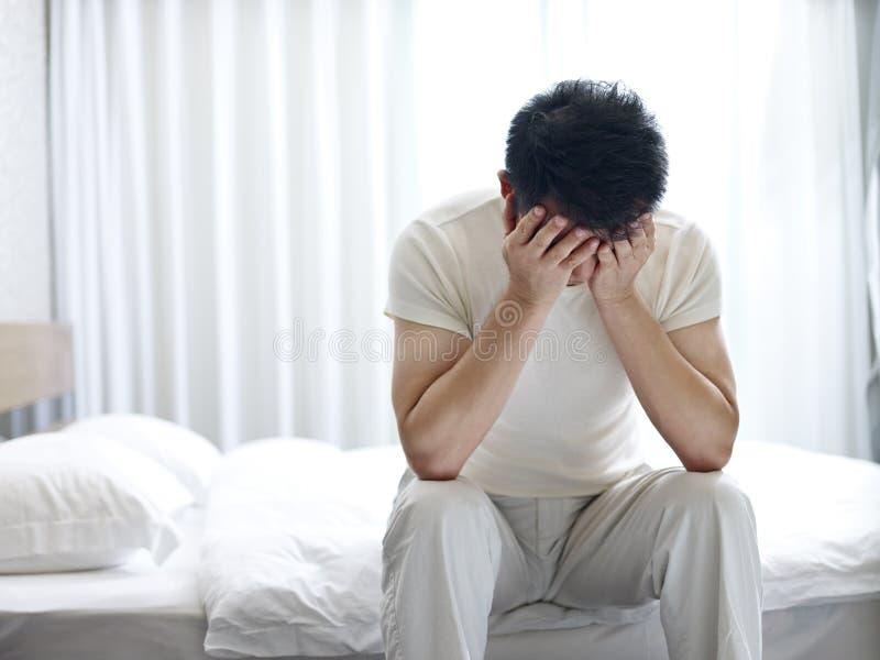 Asiatischer Mann, der unter Schlaflosigkeit leidet stockfotografie