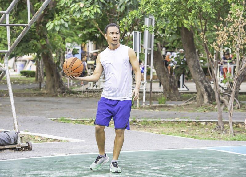 Asiatischer Mann des Basketballs in der Hand, zum des Hintergrundbaums an Knall Yai-Park, Nonthaburi auszu?ben in Thailand lizenzfreies stockfoto