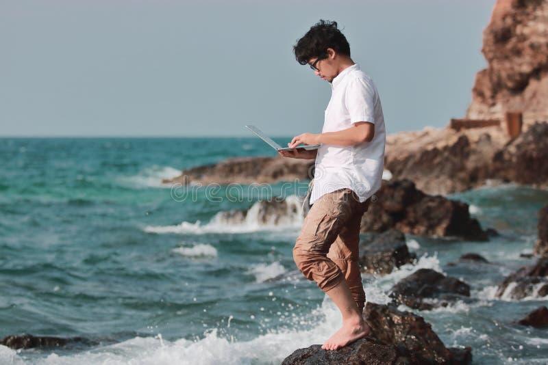 Asiatischer Mann des Lebensstils mit dem Laptop, der am blauen Seeufer sich entspannt Internet des Sachenkonzeptes lizenzfreie stockbilder