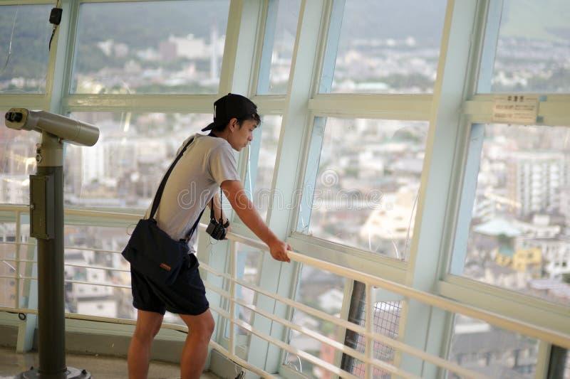 Asiatischer Mann des Porträts, der die Stadtansicht vom hohen Turm, Beppu-Turm, in Japan schaut stockfoto