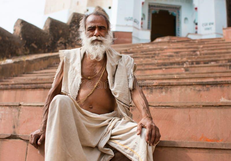 Asiatischer Mann des weißen Bartes sitzt auf den Schritten eines templ stockbilder