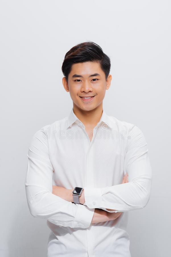 Asiatischer Mann im Hemd, schauend auf Kamera, mit den gefalteten H?nden lizenzfreie stockfotografie