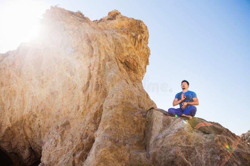 Asiatischer Mann meditiert in Yogaposition auf Hoch lizenzfreies stockfoto