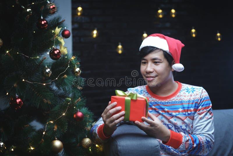 Asiatischer Mann mit dem Weihnachtskostüm, welches das Weihnachtsgeschenk sitzt neben Weihnachtsbaum hält lizenzfreies stockfoto