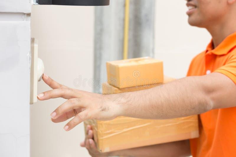 Asiatischer Mann mit Klingelnkundentürklingel des Paketkastens lizenzfreies stockbild