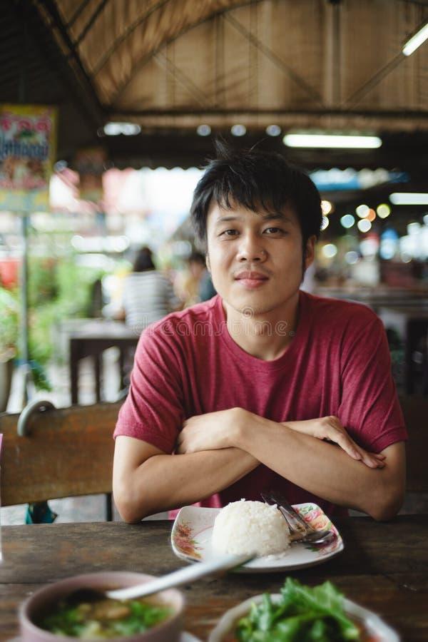 Asiatischer Mann mit Lebensmittel auf dem Tisch im Restaurant lizenzfreie stockfotografie