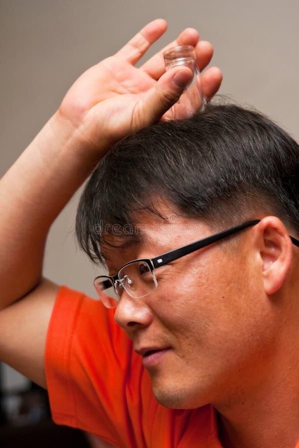 Asiatischer Mann mit Wodkaglas auf seinem Kopf stockfotografie