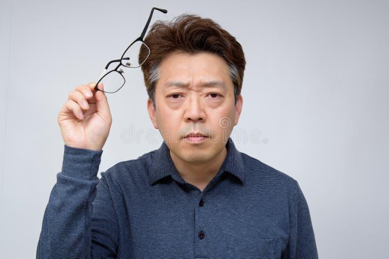 Asiatischer Mann mittleren Alters, der versucht, Brillen abzuziehen und etwas zu sehen Sehschwäche, Presbyopie, Myopie stockfoto