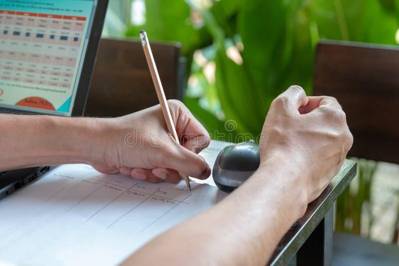 Asiatischer Mann schrieb das Budget mit einem Bleistift in seine linke Seite zum Papier, am und grünen Blatt im Freien hinten lizenzfreie stockfotografie
