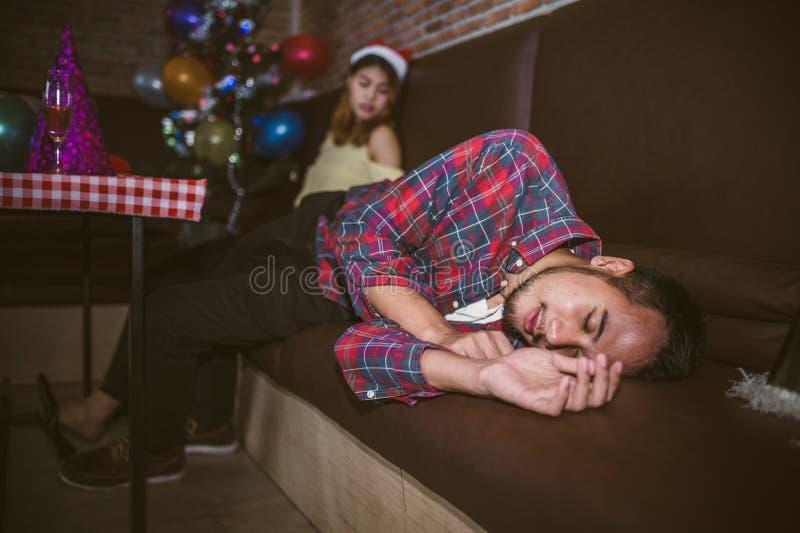Asiatischer Mann und Frauen sind sehr betrunkenes Schlafen auf der Couch nach der beendeten Partei Konzept von Weihnachtspartei u lizenzfreie stockbilder