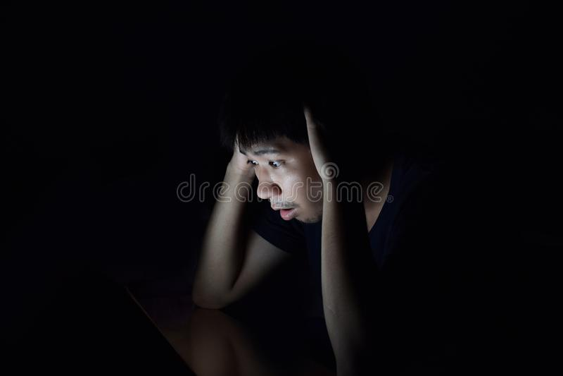 Asiatischer Mann unter Verwendung des intelligenten Telefons im schwarzen Dunkelkammer- und Gesichtsshowentsetzen lizenzfreies stockbild