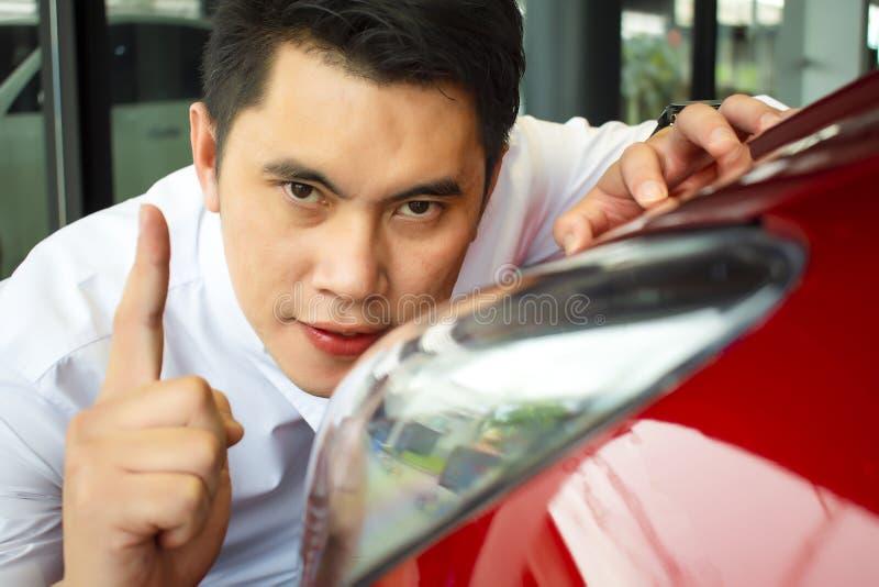 Asiatischer Mann wipping Auto mit LED-Scheinwerfer lizenzfreie stockfotografie