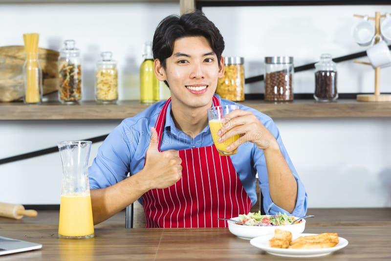 Asiatischer Manngriff ein Glas frischen Orangensaft lizenzfreies stockfoto