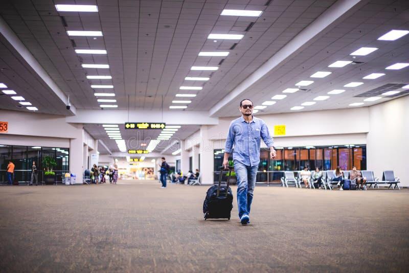 Asiatischer Mannreisender mit dem Koffergehen und -transport an einem Flughafen stockfoto