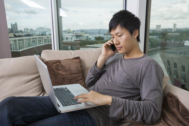 Asiatischer mittlerer erwachsener Mann beim Anruf bei der Anwendung des Laptops im Wohnzimmer stockfotografie