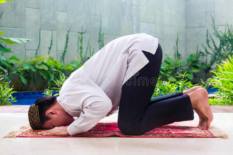 Asiatischer moslemischer Mann, der auf Teppich betet stockbild