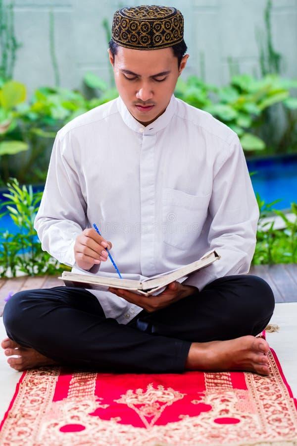 Asiatischer moslemischer Mann, der den Koran oder Quran studiert stockbilder