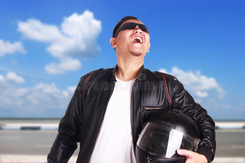 Asiatischer Motorradfahrer-Radfahrer-Rennläufer, der stolz lacht stockfotos