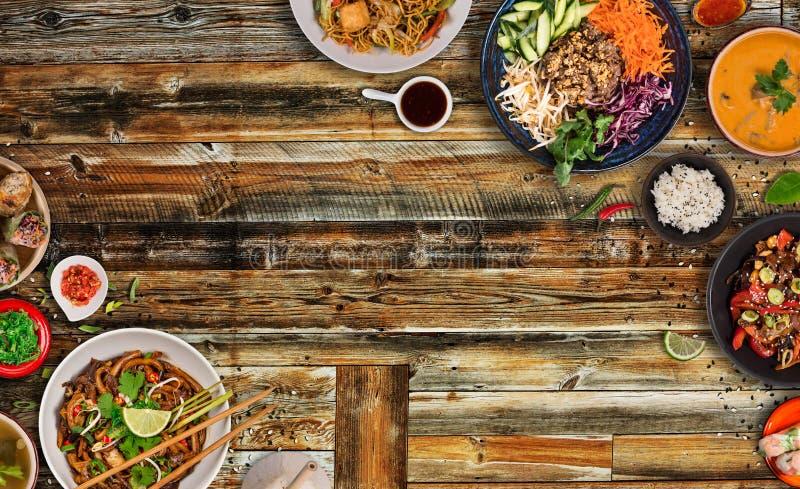 Asiatischer Nahrungsmittelhintergrund mit verschiedenen Bestandteilen auf rustikalem Holztisch, Draufsicht stockbild