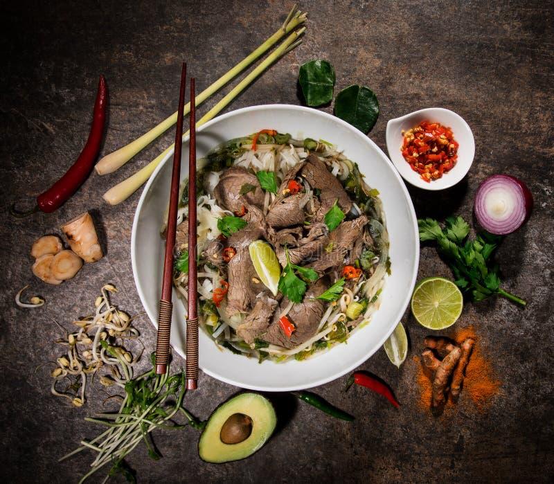 Asiatischer Nahrungsmittelhintergrund Pho BO mit verschiedenen Bestandteilen auf rustikalem Steinhintergrund, Draufsicht stockfotografie