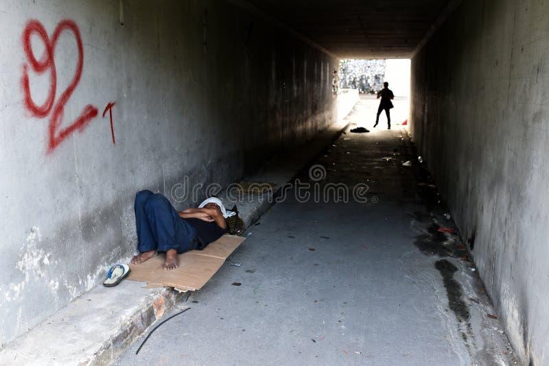 Asiatischer obdachloser Mann, der in einem Tunnel schläft stockbilder