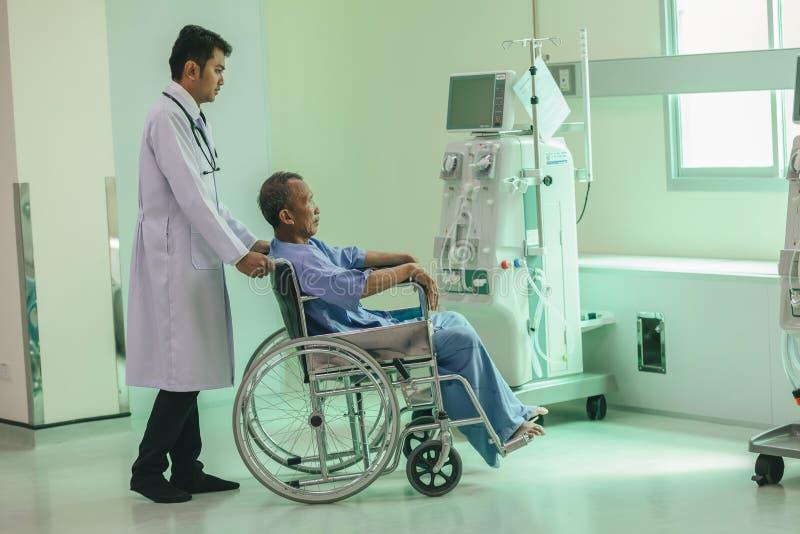 Asiatischer Patient im Rollstuhl, der im Krankenhaus mit asiatischem docto sitzt lizenzfreie stockfotografie