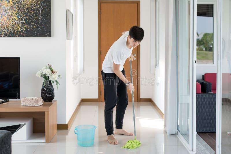 Asiatischer Reinigungsboden des jungen Mannes zu Hause lizenzfreies stockfoto