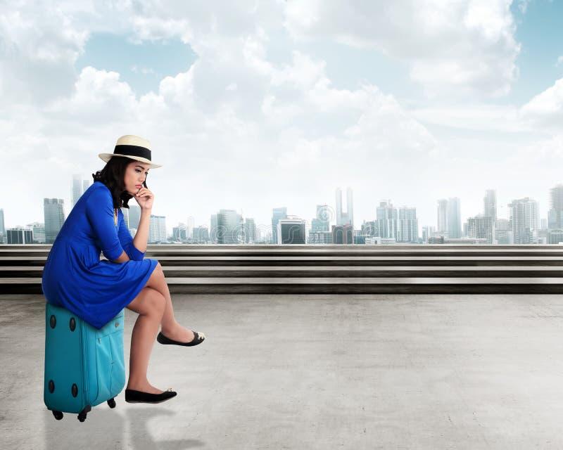 Asiatischer Reisender der jungen Frau mit dem traurigen Gesicht, sitzend auf dem Koffer stockbild