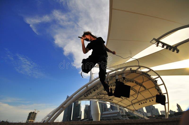 Asiatischer Rockstar, der mit Stadt als Hintergrund durchführt stockbilder
