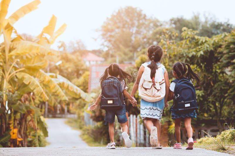 Asiatischer Schüler scherzt mit dem Rucksack, der zur Schule geht lizenzfreie stockfotografie
