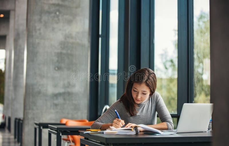 Asiatischer Student, der in der Bibliothek studiert stockfotografie