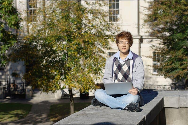 Asiatischer Student draußen mit Laptop stockfoto