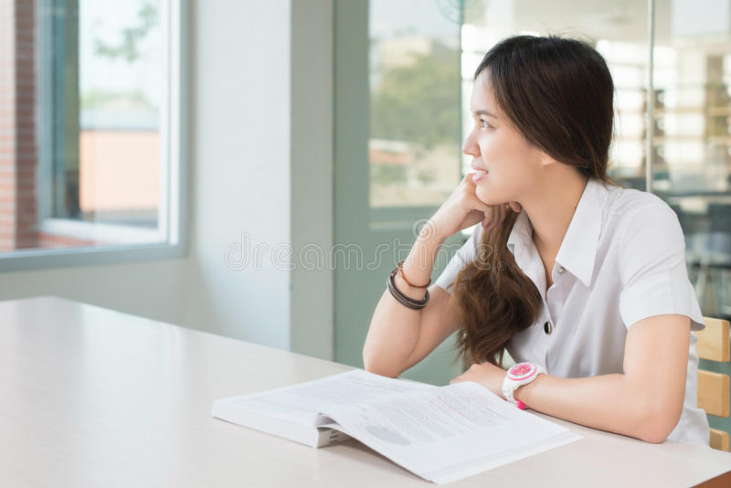 Asiatischer Student im einheitlichen Denken während Lesebuch im classroo lizenzfreies stockbild