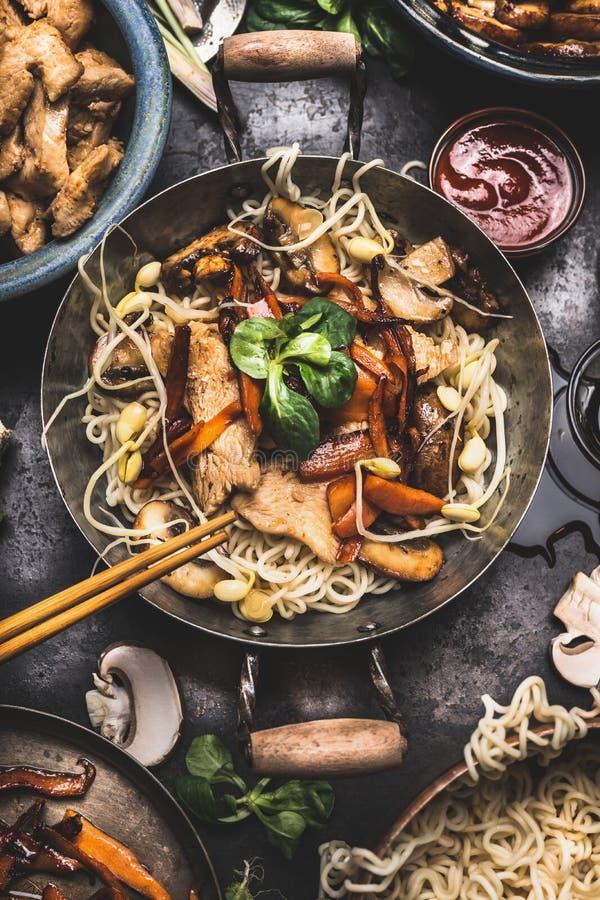 Asiatischer Teller mit Hühnergemüsenudel braten in wenigem Wok mit Essstäbchen und Kochenbestandteile an stockfotos