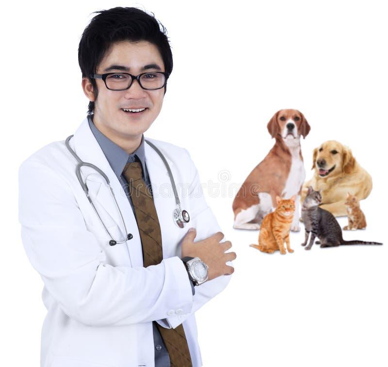 Asiatischer Tierarzt, der mit Haustier lächelt stockfotos