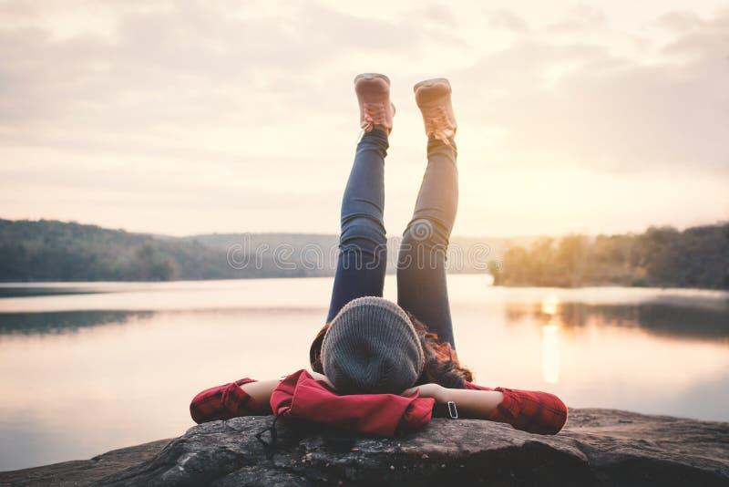 Asiatischer Tourist des entspannenden Momentes, der auf Felsenwartesonnenuntergang schläft stockfotografie
