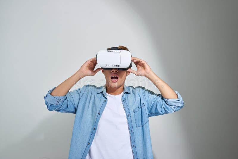 Asiatischer tragender Kopfhörer der virtuellen Realität des jungen Mannes stockfotografie