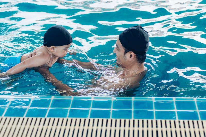 Asiatischer Vater- und BabylektionsSwimmingpool im Wasser lizenzfreie stockfotos