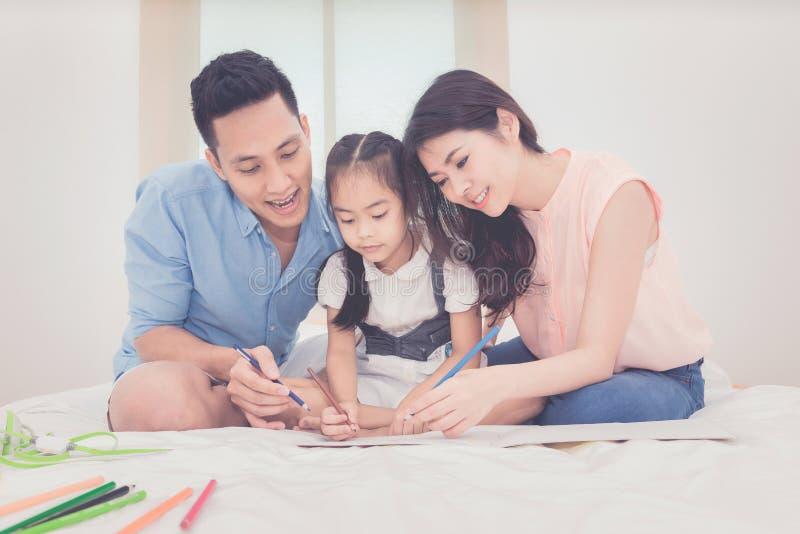 Asiatischer Vater und Mutter, die ihr Tochterkind unterrichtet stockfotografie