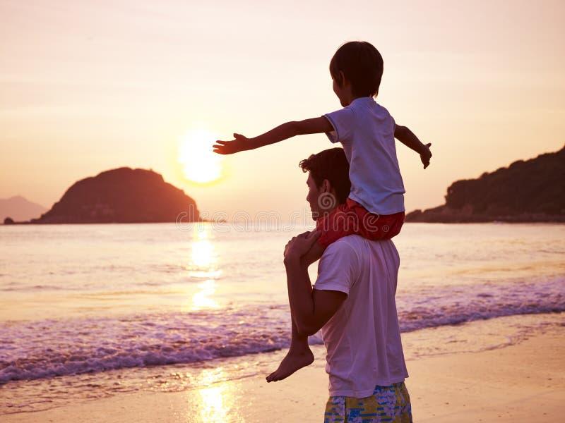 Asiatischer Vater und Sohn auf Strand bei Sonnenaufgang stockfotos
