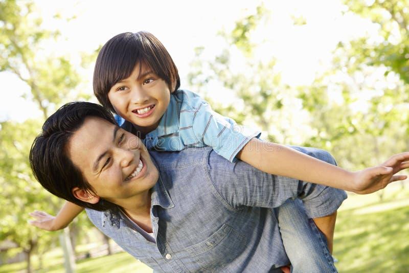 Asiatischer Vater und Sohn des Porträts, die im Park spielt stockfoto