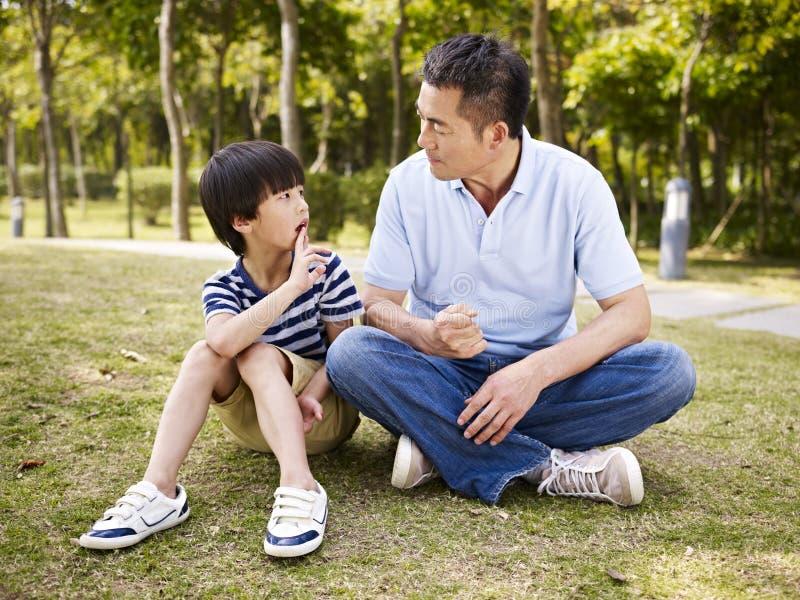 Asiatischer Vater und Sohn, die ein Gespräch hat stockbild